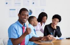 Smart afrikansk amerikanaffärsman med affärslaget på kontoret arkivfoto