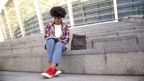 Smart afro--amerikan studenthandstil i anteckningsboken som g?r l?xa n?ra stadion arkivbild