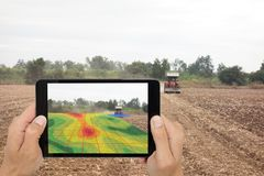 Smart agriculture concept, farmer use tablet read infrared in tr. Actor with high definition soil mapping while planting,conduct deep soil scan during a tillage Royalty Free Stock Images