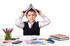 Smart allvarlig utmärkt elev på skrivbordet med den öppna boken på huvudet på den vita bakgrunden Arkivfoton