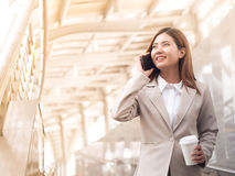 Smart asian business woman in a suit with mobile phone. Smart asian business woman in a suit with mobile phone and holding a paper cup of coffee, outside Stock Photo