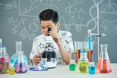 Handsome Pupil Using Microscope. Smart Asian pupil sitting at desk and using microscope while studying chemical substance at science classroom, blackboard on Stock Images