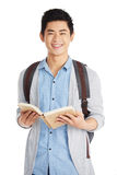 Smart Asian Student with Book. Waist-up portrait of Asian university student distracted from reading book and looking at camera with wide smile, isolated on Stock Photos