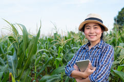 Smart Asian woman farmer in corn field. With digital tablet - agriculture farming small business owner concept Stock Photo