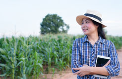 Smart Asian woman farmer in corn field. With digital tablet - agriculture farming small business owner concept Royalty Free Stock Images