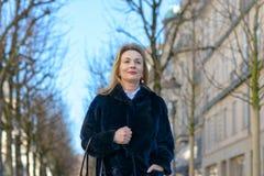 Smart attraktiv blond kvinna i ett varmt vinterlag fotografering för bildbyråer