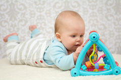 Smart baby girl. Cute baby lying on belly  on soft surface and intently playing with her colorful toys Stock Image