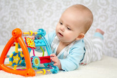 Smart baby girl. Cute baby lying on belly  on soft surface and intently playing with her colorful toys. Close up portrait Royalty Free Stock Images