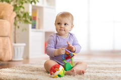 Smart baby with educatinal toys in sunny nursery room Stock Photography