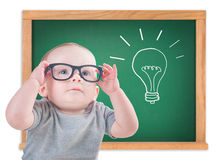 Smart baby with glasses and an idea. On a chalkboard royalty free stock photo