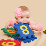 Smart baby nibbling figures and numbers Royalty Free Stock Photos