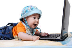 Smart baby is working on laptop. Little baby is pushing laptop`s keyboard and he is looking at the screen absolutely amazed  on white background Stock Photos