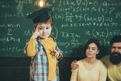 Smart barn, wunderkind i doktorand- lock som pekar på hans huvud Pojke som framlägger hans kunskap till mamman och farsan föräldr Arkivbild