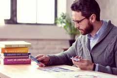 Smart bearded fortune teller looking at tarot cards. Future and destiny. Smart bearded fortune teller looking at tarot cards while wanting to know the destiny stock photo