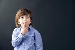 Smart beautiful kid thinking against a black background Stock Image