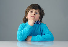 Smart beautiful kid thinking against grey background Royalty Free Stock Images