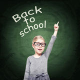 Smart beautiful little girl on the chalkboard background Royalty Free Stock Photography