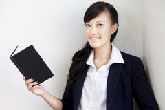 Smart, beautiful young chinese lady reading. A young, beautiful and smart chinese lady reading book and smiling while looking into the camera Stock Images