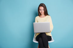 Smart beautiful young girl using laptop over blue background Royalty Free Stock Photos