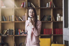 Smart beautiful young woman in headphones with a glass of coffee Royalty Free Stock Images