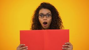 Smart biracial female millennial shocked with scientific facts, holding red book. Stock footage stock video footage