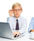 Smart blond boy pretending to be a boss. Working on computer as he plays to be adult like father Stock Image