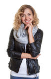 Smart blond woman in a leather jacket Royalty Free Stock Images