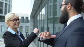 Smart blonde woman giving male colleague high-five gesture, business winners