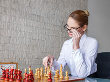 Smart blonde woman playing chess Royalty Free Stock Photography