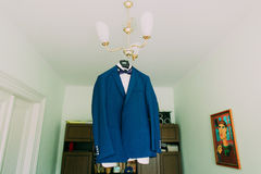 Smart blue men's blazer with white shirt and tie on hanger in the interior Stock Photography
