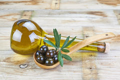 Smart bottle of olive oil and spoon with olives. Smart bottle of olive oil and wooden spoon with black olives Stock Images