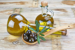 Smart bottle of olive oil and spoon with olives. Smart bottle of olive oil and wooden spoon with black olives Stock Image