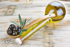 Smart bottle of olive oil and spoon with olives Royalty Free Stock Photos