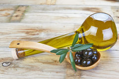 Smart bottle of olive oil and spoon with olives Stock Images