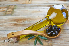 Smart bottle of olive oil and spoon with olives. Smart bottle of olive oil and wooden spoon with black olives Royalty Free Stock Photography