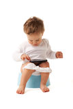 Smart boy. Boy sitting on a chamber pot playing with smartphone Stock Photography