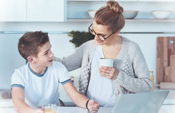 Smart boy asking mom for help with home assignment. Mother is the best teacher. Beaming mother holding a cup of tea and embracing her son while giving him royalty free stock image