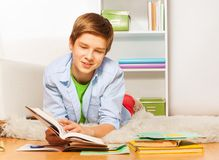 Smart boy with book and textbook lay on the floor Royalty Free Stock Photos
