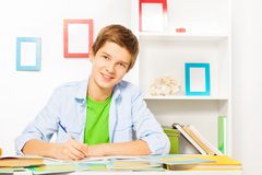Smart boy with books and textbooks on the table. Handsome nice boy with textbooks writing doing homework sitting by the table at home Stock Image