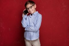 Smart boy in eyeglasses talking by mobile phone. stock images