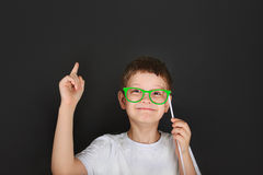 Smart boy with green glasses is thoughtful near chalkboard. Stock Photos