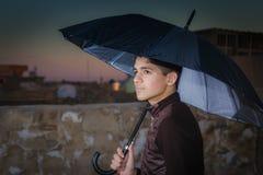 Smart boy holding an umbrella Stock Photos