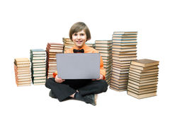 A smart boy with a laptop sits at the stacks of books Stock Photo