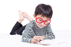 Smart boy learn to write. On the bed Royalty Free Stock Photos