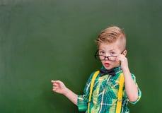 Smart boy points on empty green chalkboard Stock Photography