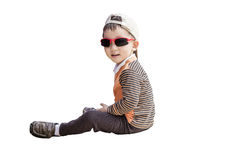 Smart boy sitting on the ground and wearing sunglasses Royalty Free Stock Photography