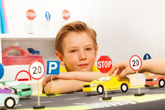Smart boy sitting at the road playing field Royalty Free Stock Photo