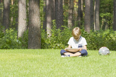 Smart boy using a tablet outdoors. Technology, lifestyle, education, people concept Stock Image