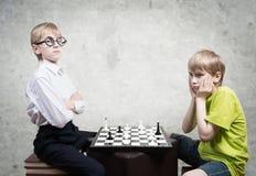 Smart boy vs stupid boy. Smart boy playing chess against stupid boy, studio shot royalty free stock photos