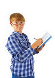 Smart boy wearing glasses is writing in a book Stock Photo